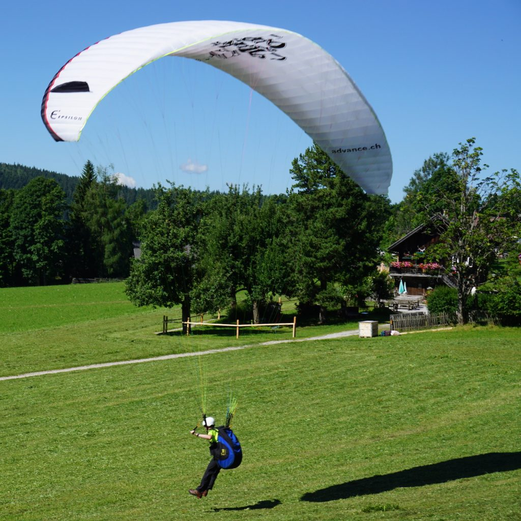 White paraglider while paragliding in Schladming