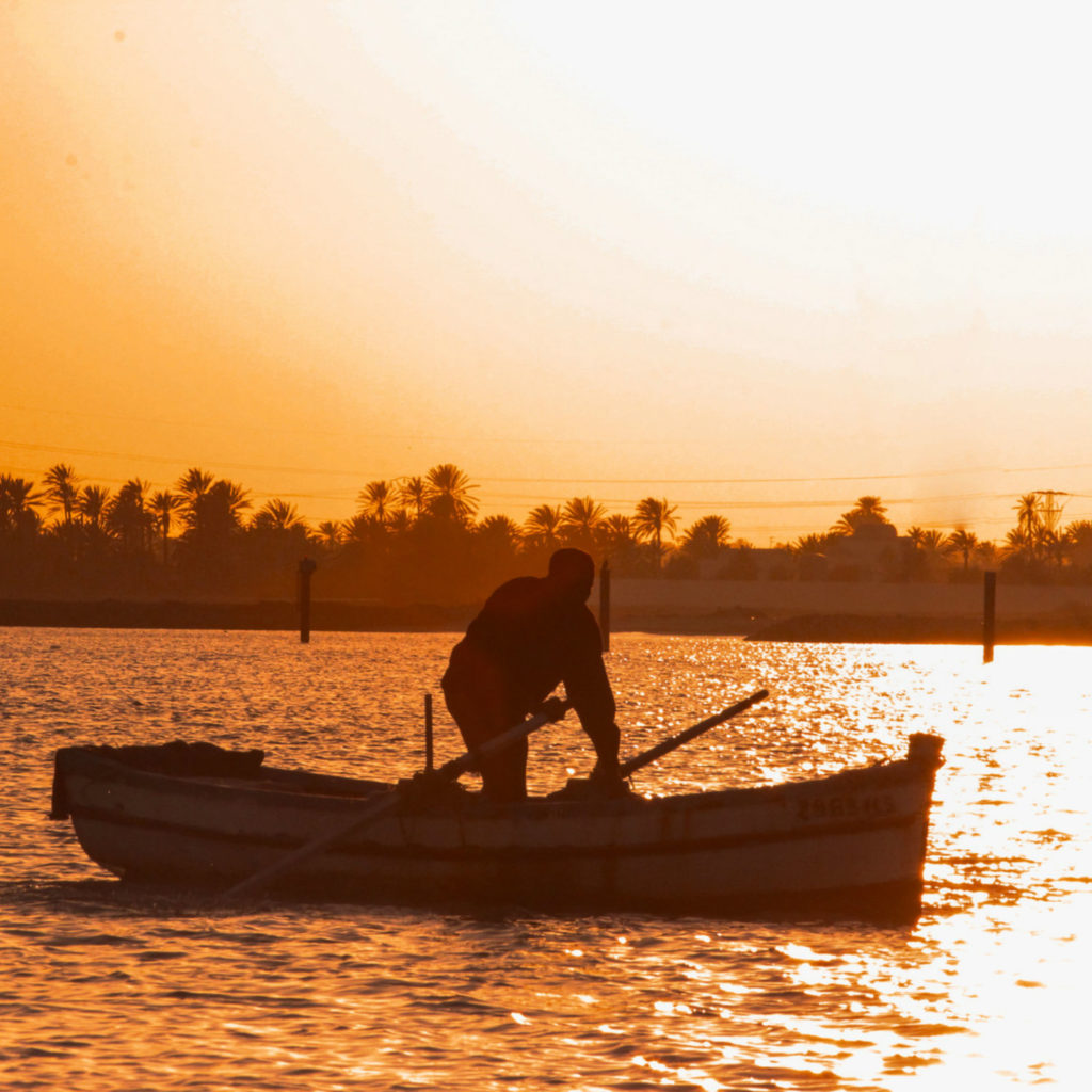 Boatman on a wooden boat at sunset