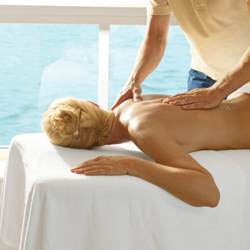 Woman getting a back massage by the sea