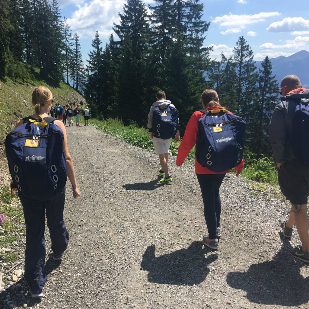 Teilnehmer steigen über Bergweg zur Zipline auf