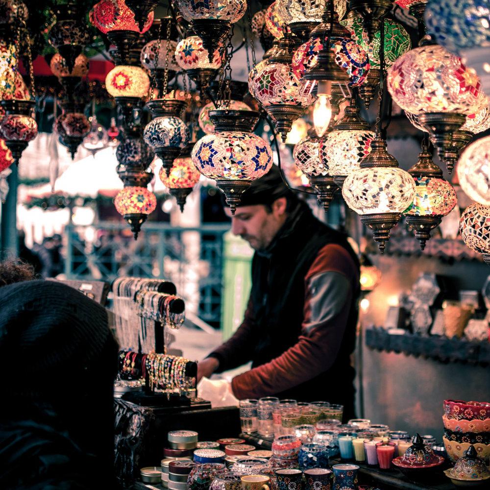 Mann hinter Stand auf dem Markt mit Keramik und Lampen