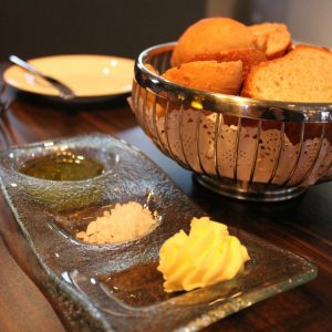 Brotkorb mit Salz, Butter und Olivenöl