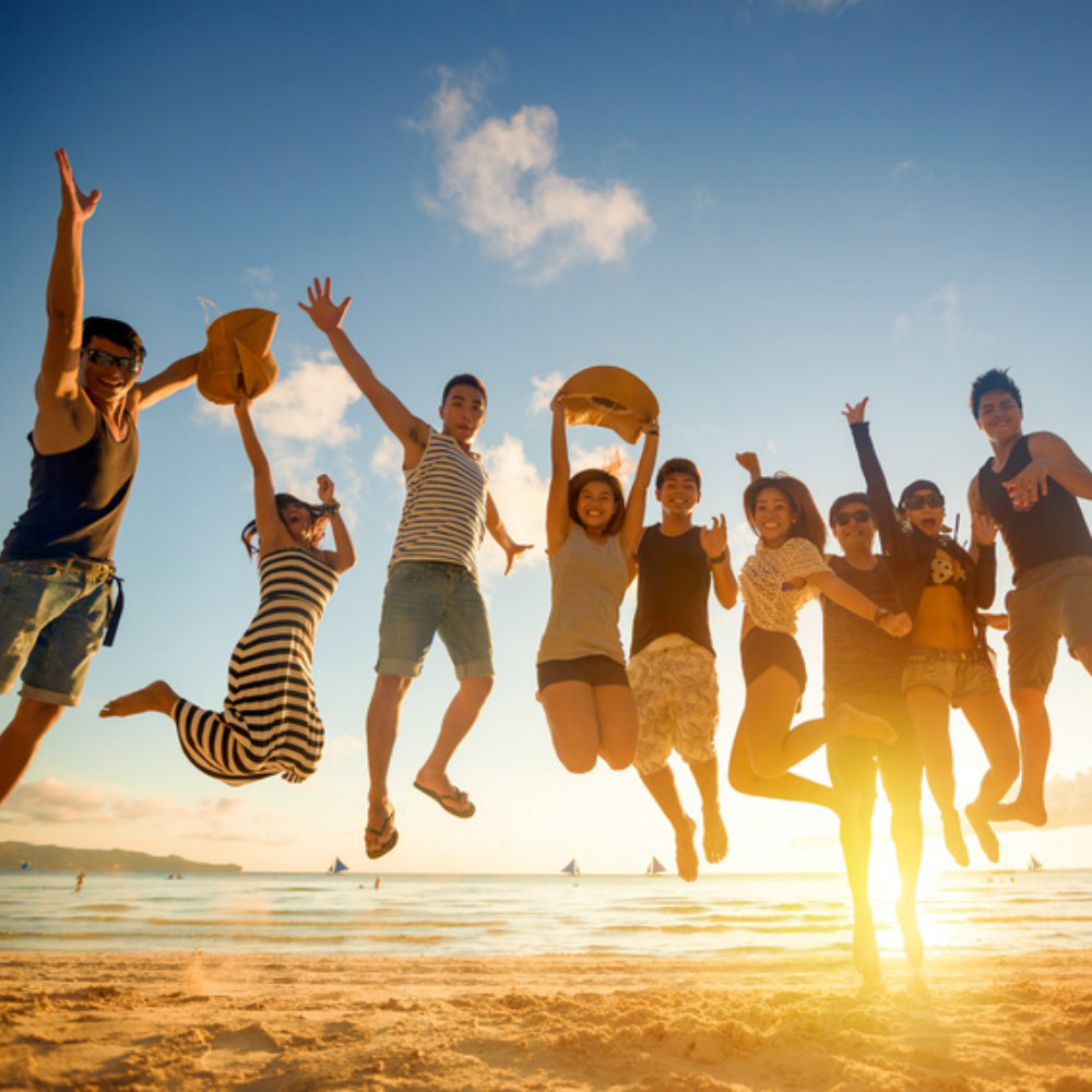 Group of young people jumps on the beach