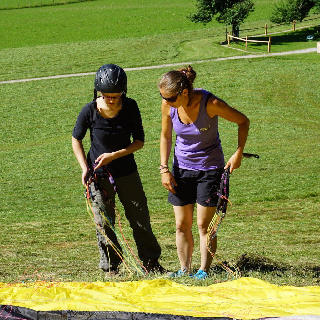Miri und Paragliding Lehrerin Sandra ordnen Leinen des Gleitschirms