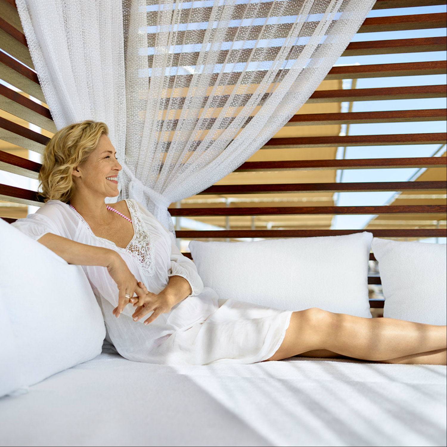 Blonde woman relaxing in a daybed before check-out