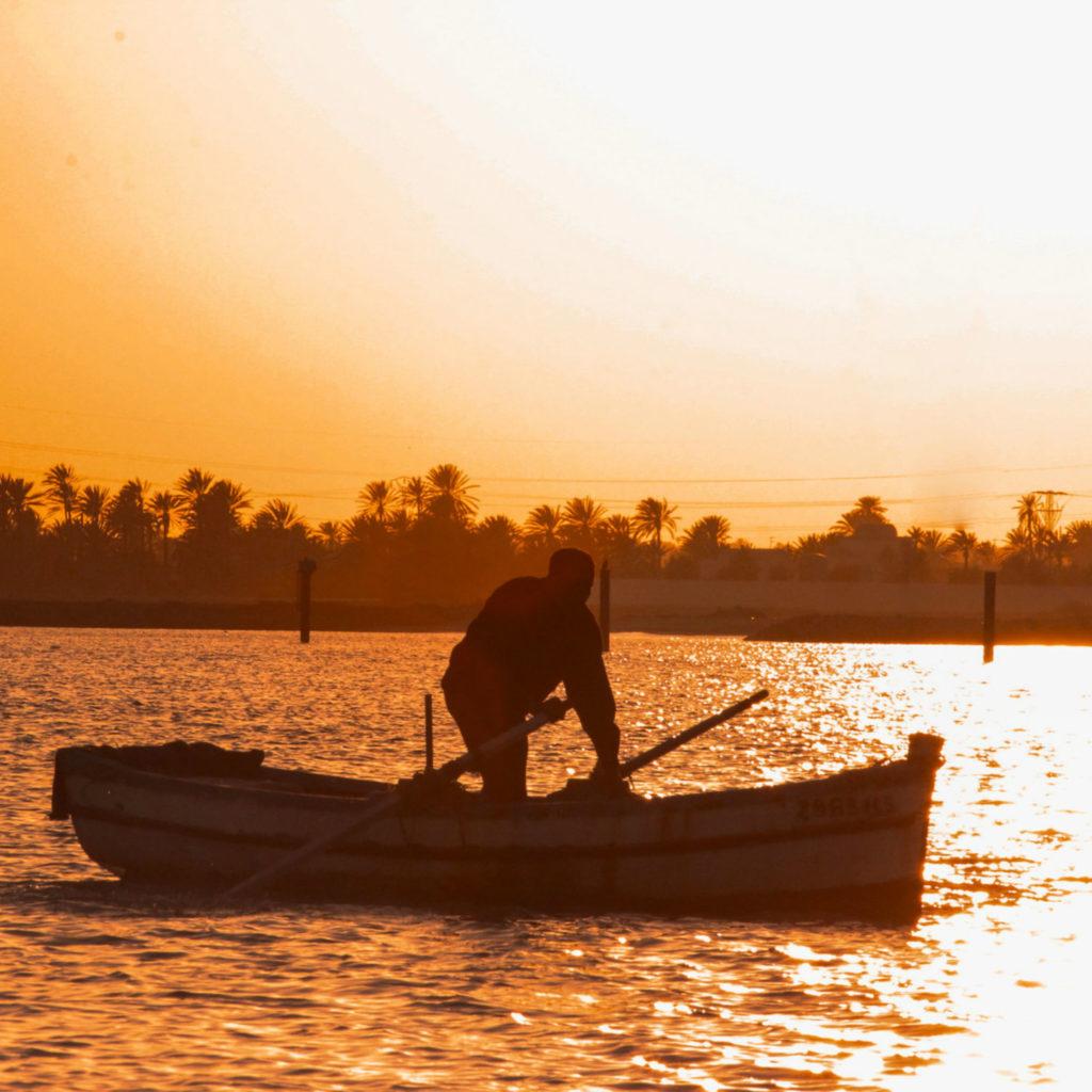 Bootsmann auf Holzboot bei Sonnenuntergang