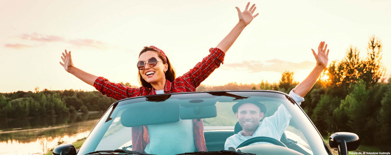 Couple in car throw their arms in the air