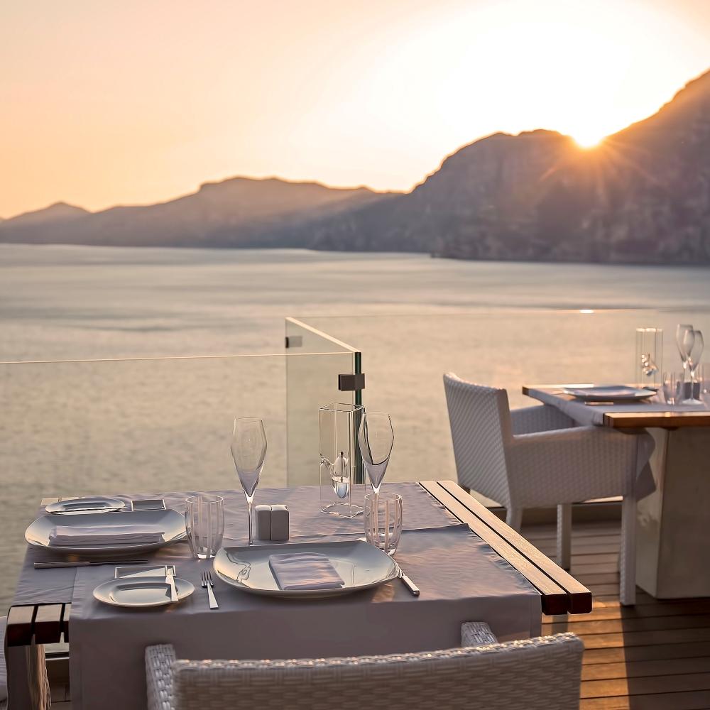 Terrasse eines Restaurants mit Blick auf das Meer, den Sonnenuntergang und die Amalfiküste
