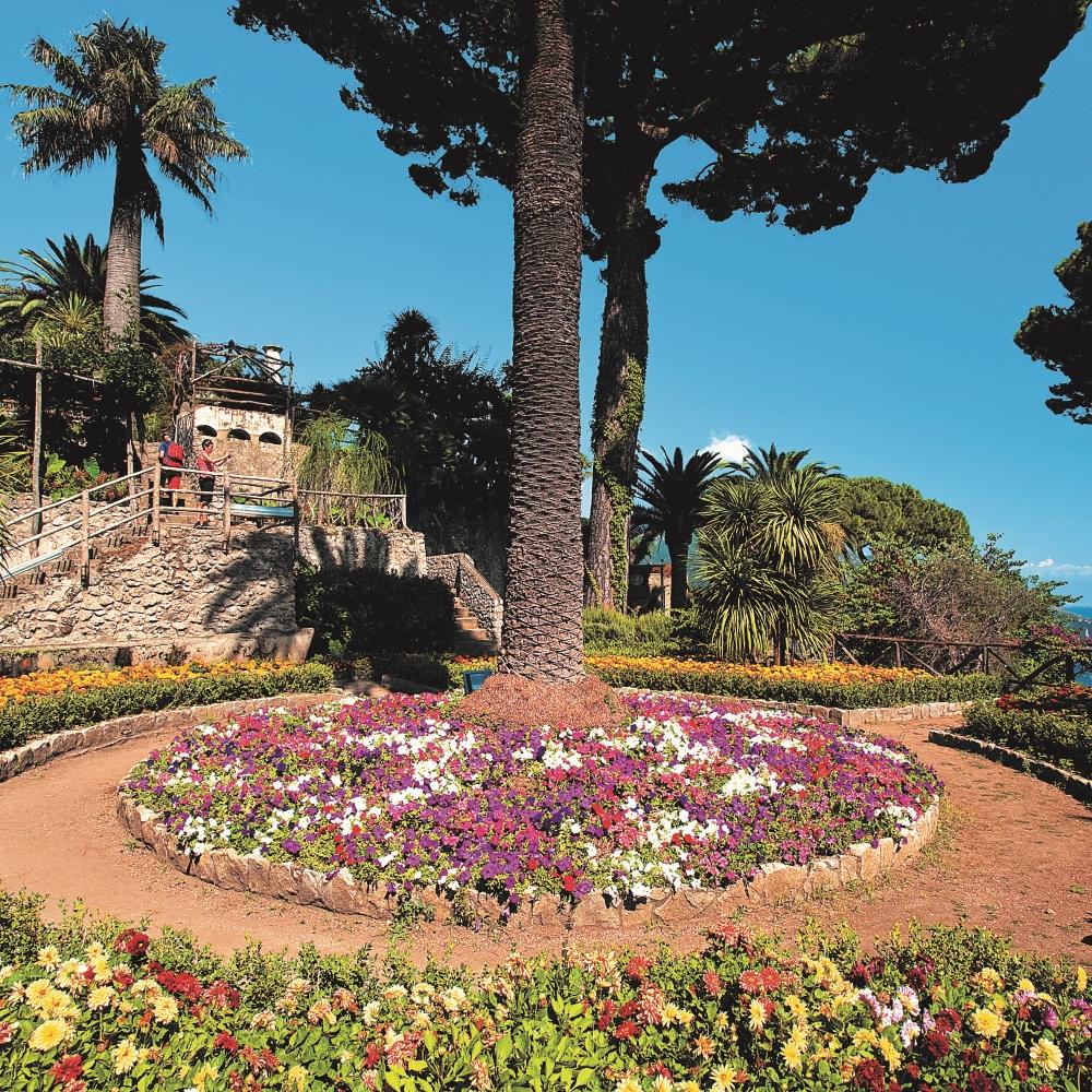 Garten mit vielen bunten Blumen und Palmen