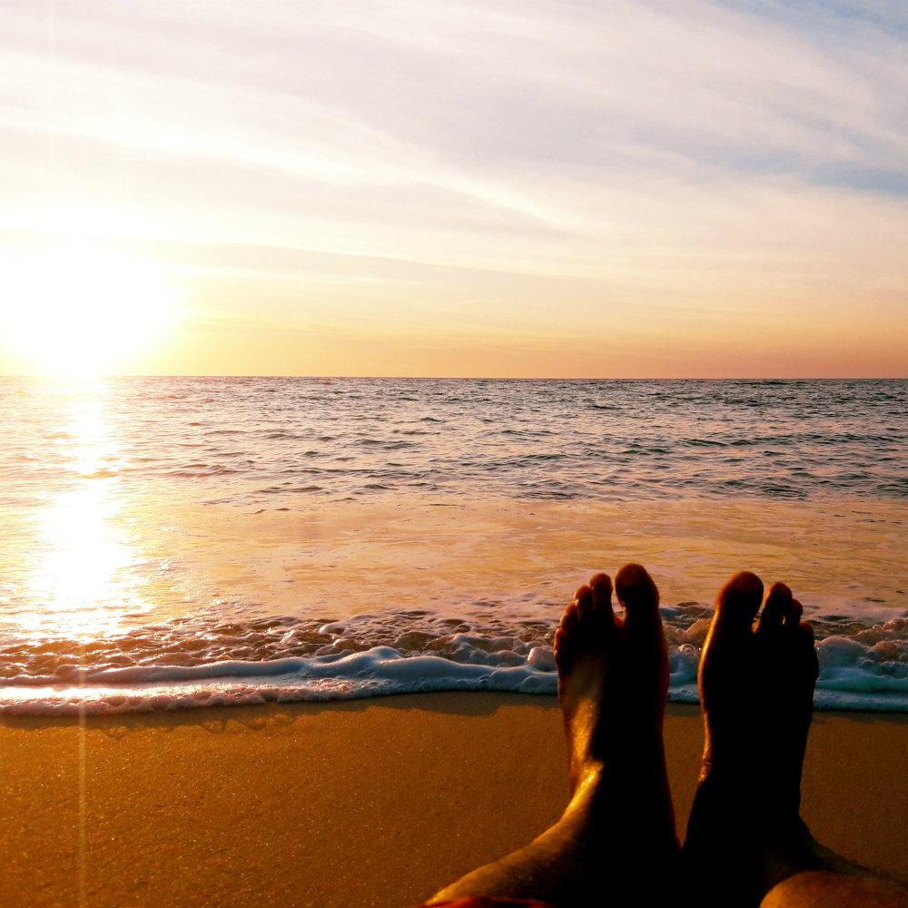 Sonnenuntergang am Strand Füße vor Meer
