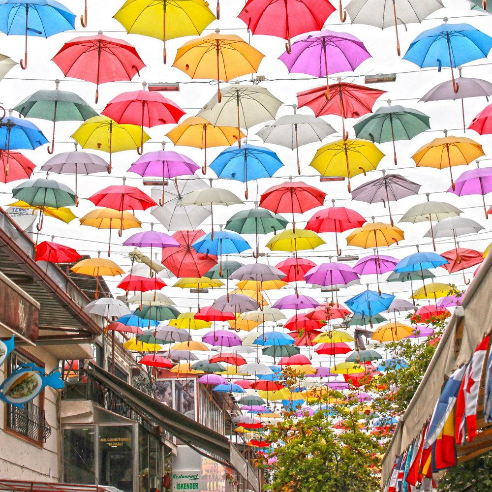 Straße mit aufgespannten Regenschirmen