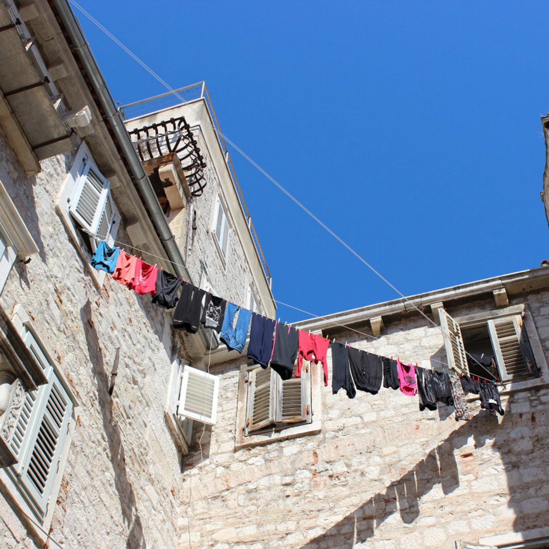 Wäscheleine hängt zwischen Häuserwänden