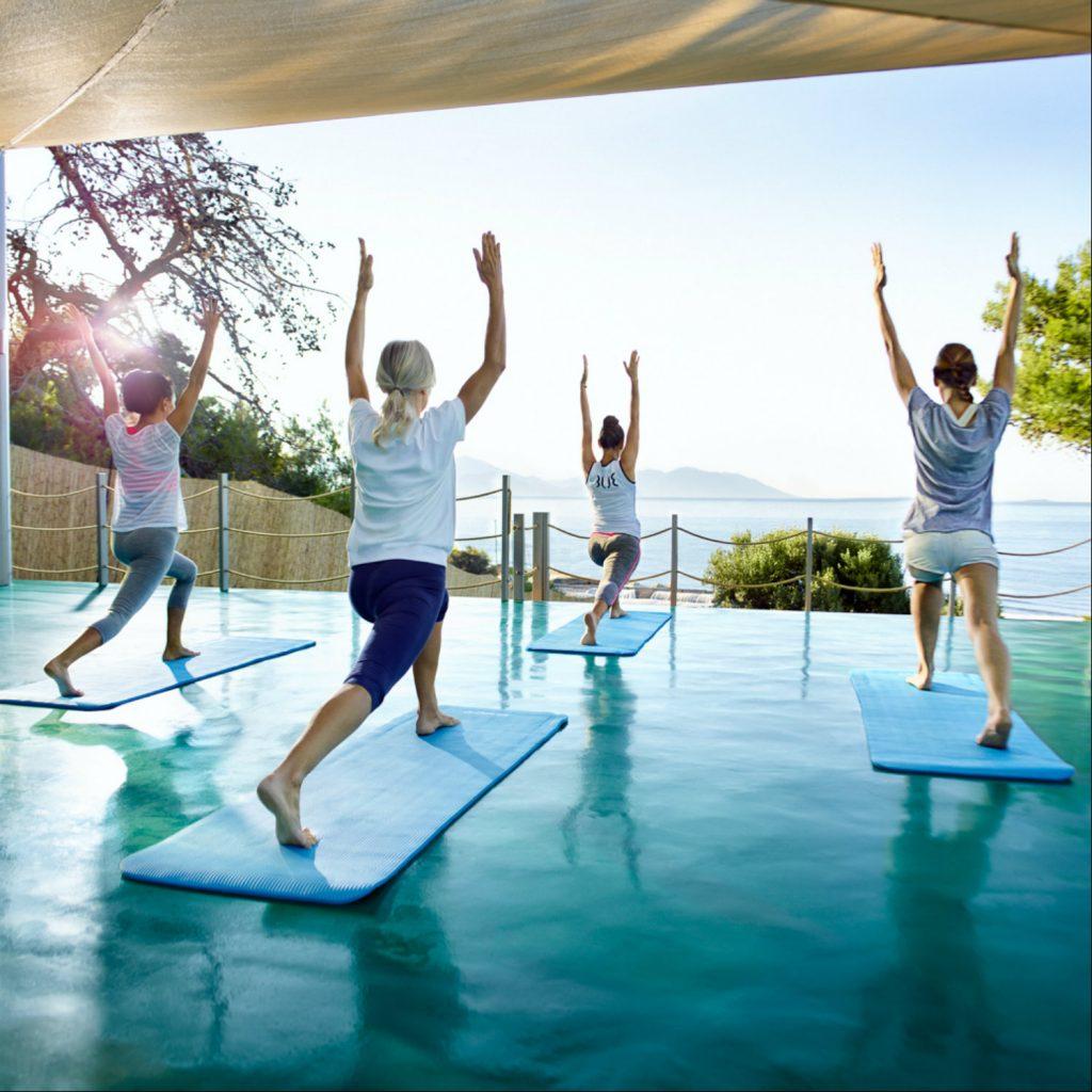 Gruppe beim Yoga mit Meerblick