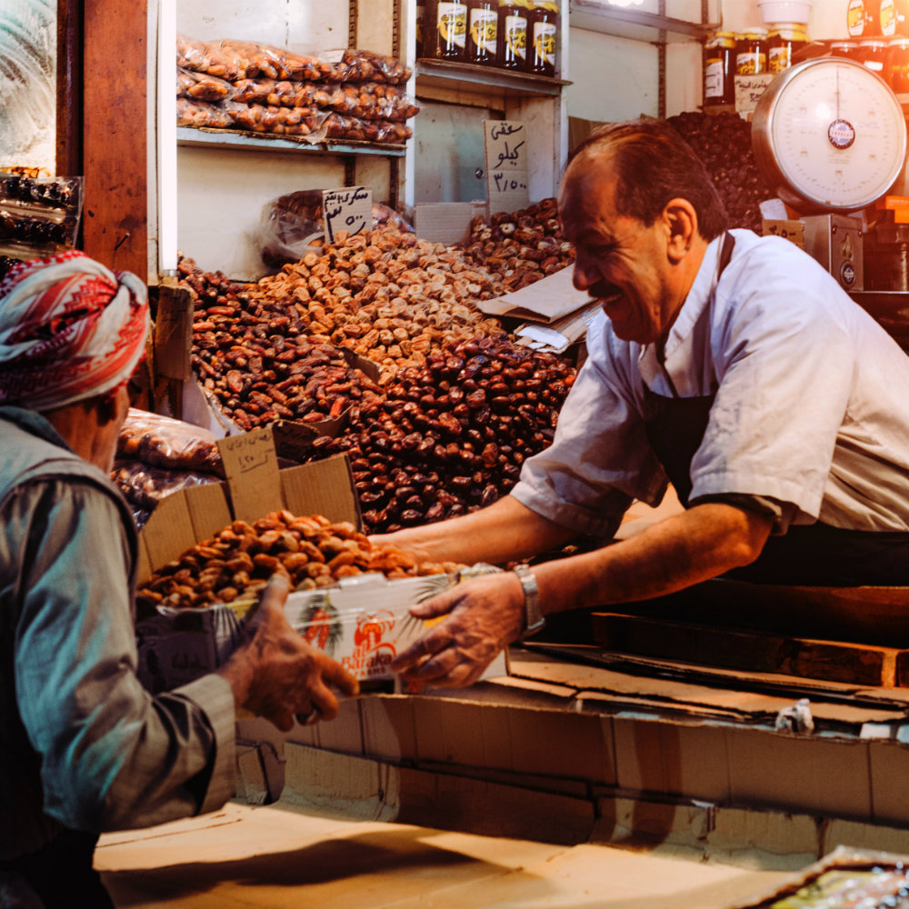 zwei Männer an Marktstand Produkte werden ausgetauscht