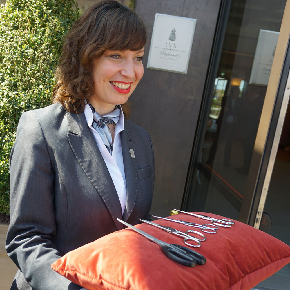 5 Sterne Hotel Toskana Il Castelfalfi Banddurchscheidung Scheren auf rotem Kissen