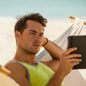Mann mit Tablet am Strand