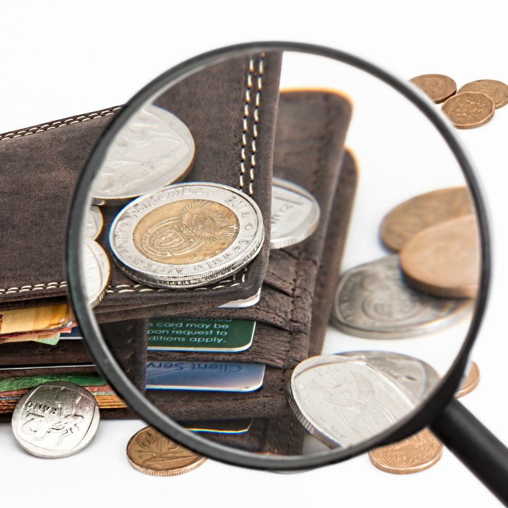 Geldbörse Münzen mit einer Lupe