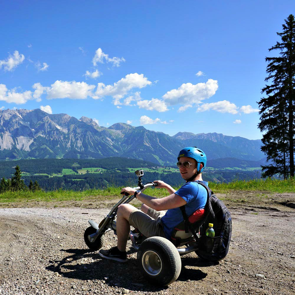 mountaincarting in front of an alpine panorama