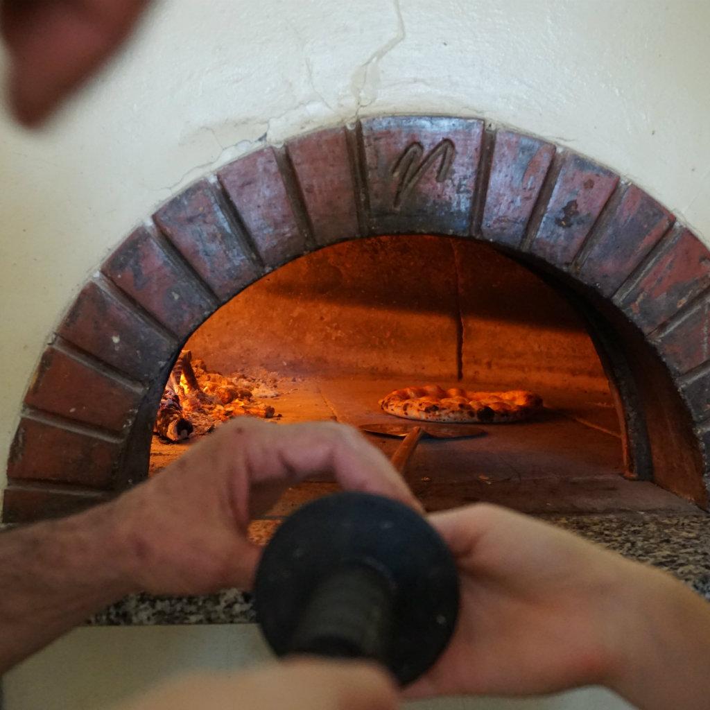 Pizza wird in Steinofen geschoben