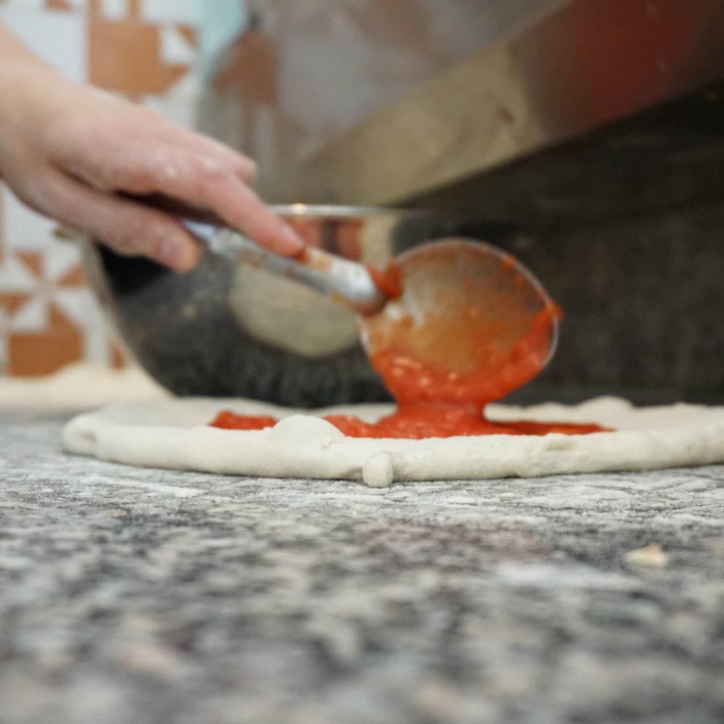 Spread the tomato sauce on the pizza dough