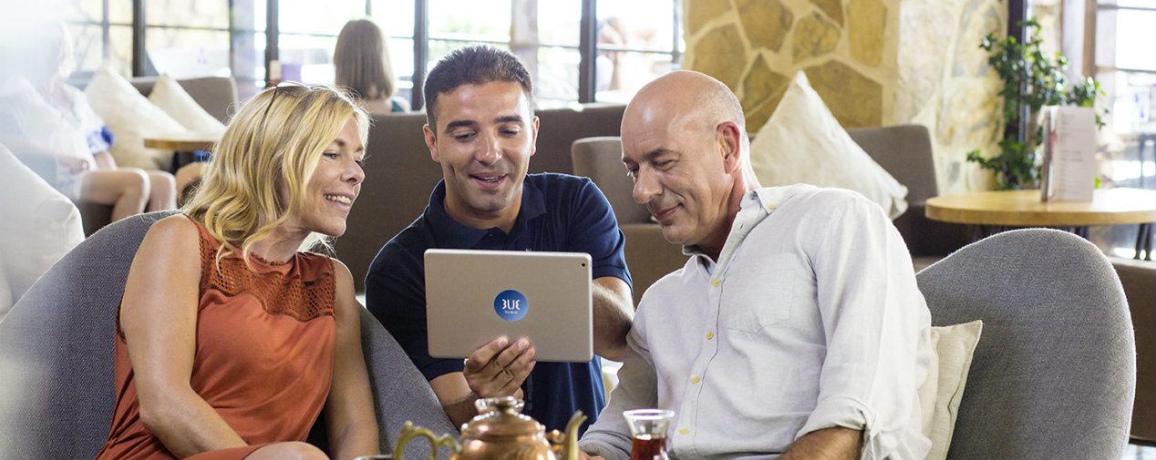 TUI BLUE Guide schaut mit zwei Gästen auf ein Tablet